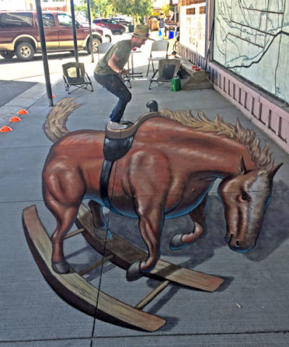 picture of the artist standing in the saddle of his street chalk art creation of a bucking bronco rocking horse